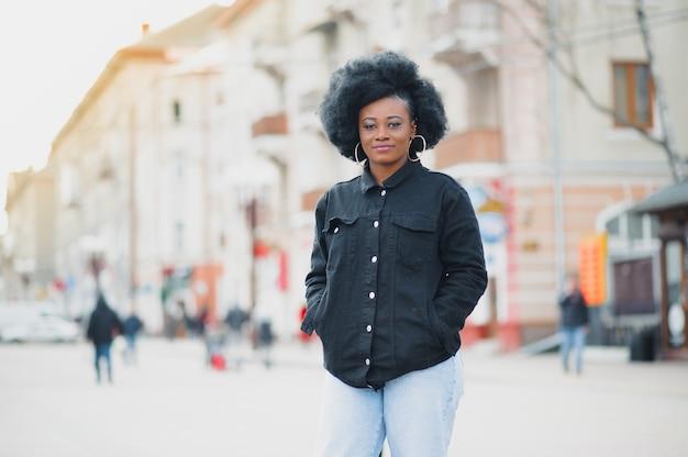 Красивая девушка с афро-стрижкой гуляет по улице