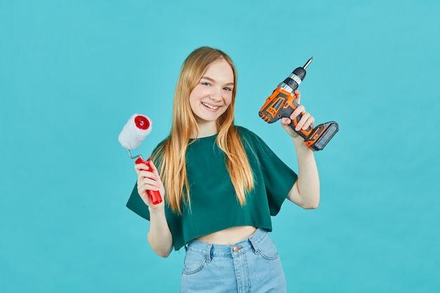전기 드라이버와 파란색 벽에 페인트 롤러 아름 다운 소녀. 리노베이션 아파트 룸용 악기 액세서리. 수리 집 개념.