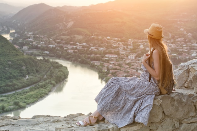 Красивая девушка с рюкзаком и шляпой сидит и любуется видом на реку, горы и город внизу