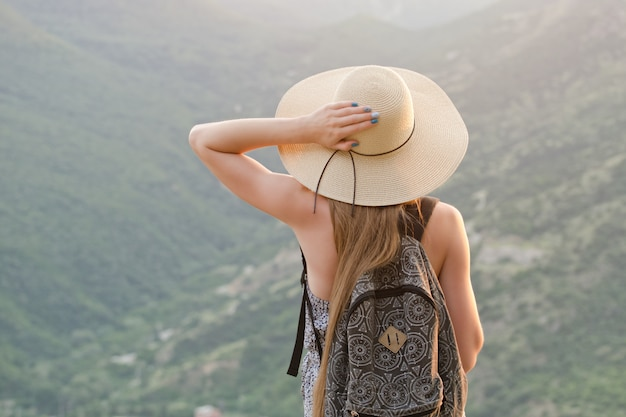 Beautiful girl with a backpack and a wide hat standing at the green mountains