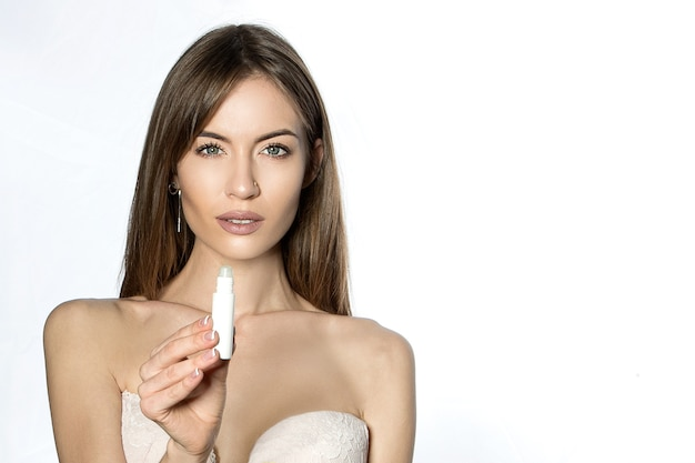 Красивая девушка с открытыми плечами рекламирует косметику на белом.