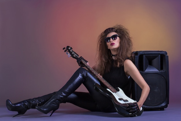 Beautiful girl with bass guitar in leather clothes.