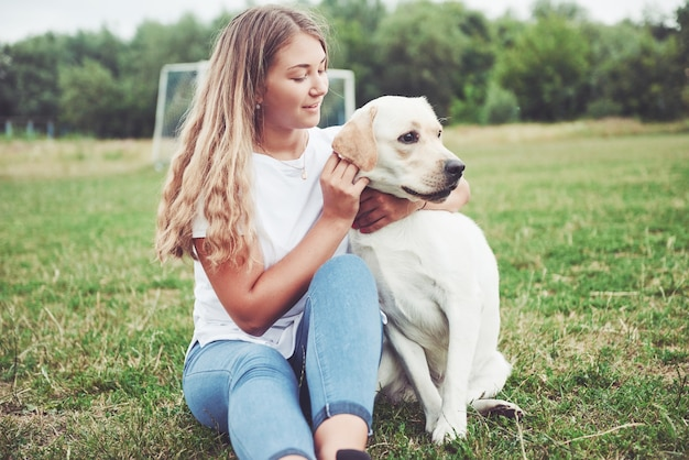 Beautiful girl with a beautiful dog in a park on green grass.