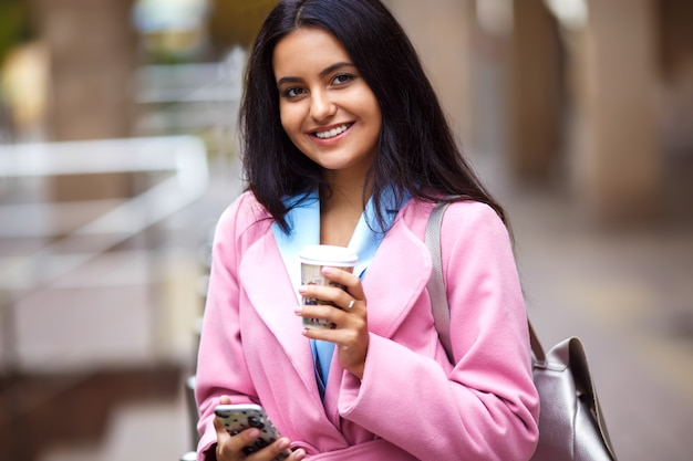 A beautiful girl with a beautiful smile talking on the phone. young beautiful pretty girl walking along the street with handbag and cup of coffee and phone in her hands