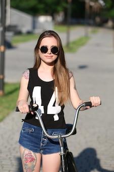 Красивая девушка с велосипедом, на открытом воздухе