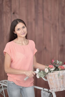 Beautiful girl with a bike carrying a beautiful basket full of flowers