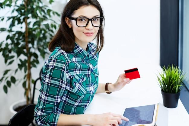 タブレットとコーヒー、フリーランスのコンセプト、クレジットカード、オンラインショッピング、肖像画を持ってカフェに座っているシャツと眼鏡を身に着けている黒い髪の美しい少女。