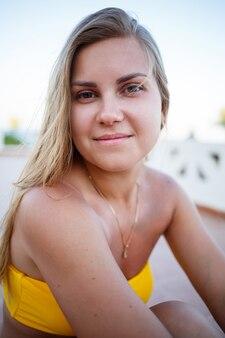 ブロンドの髪と黄色い水着の美しい少女は海に面したテラスでリラックス