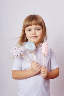 Красивая девушка со светлыми волосами ест леденец, круглую карамель на палочке в руках веселой улыбающейся девушки. девочка с длинными волосами в белой футболке лижет леденец. россия, свердловск, 1 декабря 2018 г.