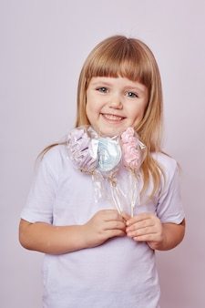 Beautiful girl with blond hair eats a lollipop, round caramel on stick in hands of cheerful smiling girl. baby girl with long hair in white t-shirt licks lollipop.