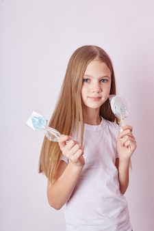 Beautiful girl with blond hair eats a lollipop, round caramel on stick in hands of cheerful smiling girl