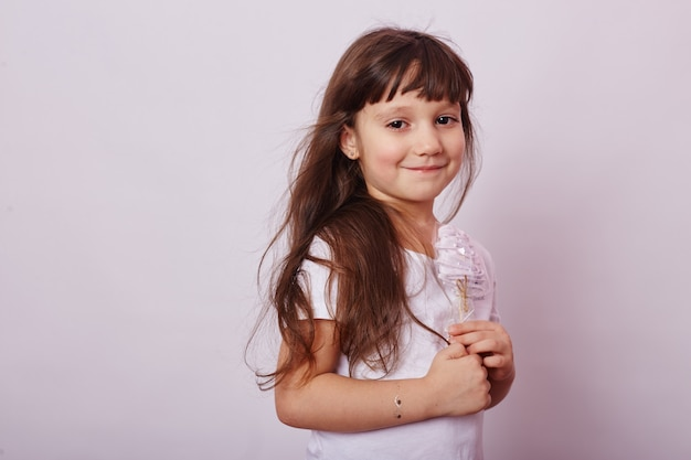 Beautiful girl with blond hair eats a lollipop, round caramel on stick in hands of cheerful smiling girl.