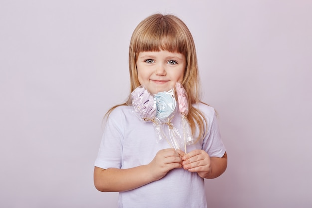 Beautiful girl with blond hair eats a lollipop, round caramel on stick in hands