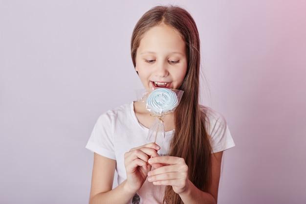 Beautiful girl with blond hair eats a lollipop