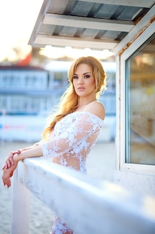 Beautiful girl with blond hair in elegant lace dress posing besi