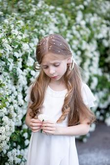 Красивая девушка со светлыми длинными волосами в белом нежном шелковом платье стоит в парке
