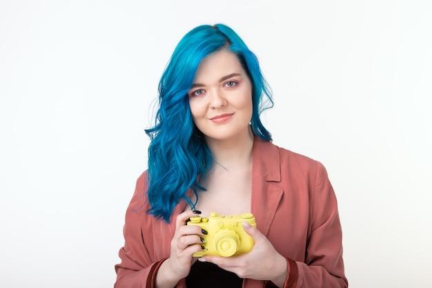 Красивая девушка с синими волосами держит желтую ретро-камеру на белой стене