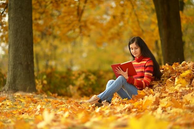 Красивая девушка с книгой в осеннем парке