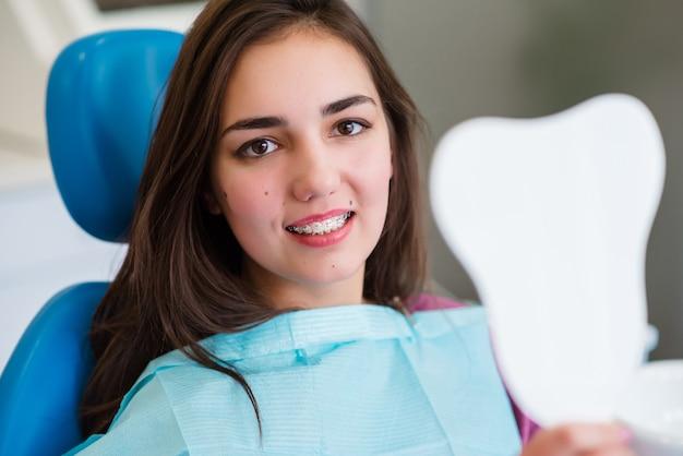 Красивая девушка с брекетами улыбается в стоматологии.
