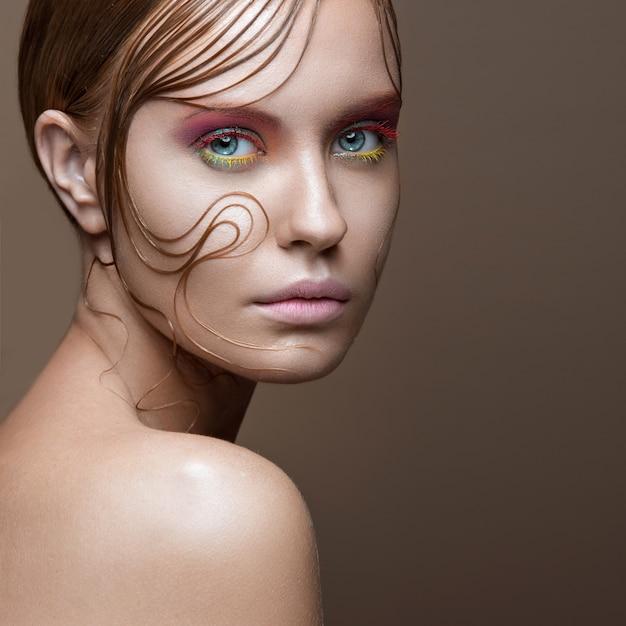 밝은 색의 메이크업과 얼굴에 머리카락의 젖은 가닥으로 아름 다운 여자.