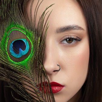 Beautiful girl with bright colored makeup and peacock feather on her face. beauty concept, close-up.