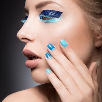 밝고 창조적 인 패션 메이크업과 파란색 매니큐어와 아름 다운 여자.