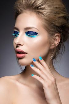 Beautiful girl with bright creative fashion makeup and blue nail polish.