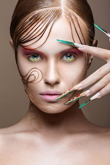 Beautiful girl with bright fashion make-up, creative hairstyle, long nails.
