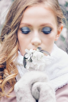Beautiful girl with bright make-up in a warm scarf and mittens holding flowers