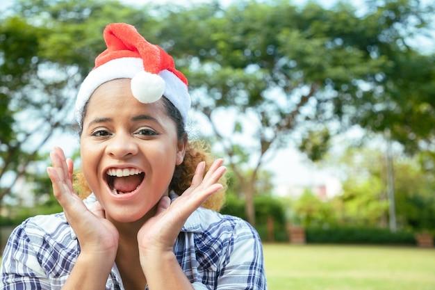 家の前の庭でサンタクロースの帽子をかぶった明るい笑顔の美しい少女。