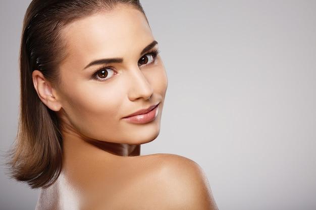 갈색 머리, 깨끗하고 신선한 피부와 회색 벽에 포즈를 취하는 벗은 어깨를 가진 아름다운 소녀, 가벼운 누드 메이크업 모델을 닫습니다.