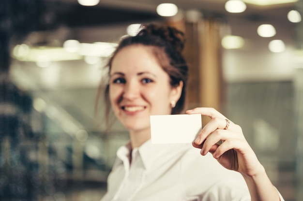Beautiful girl with a business card.