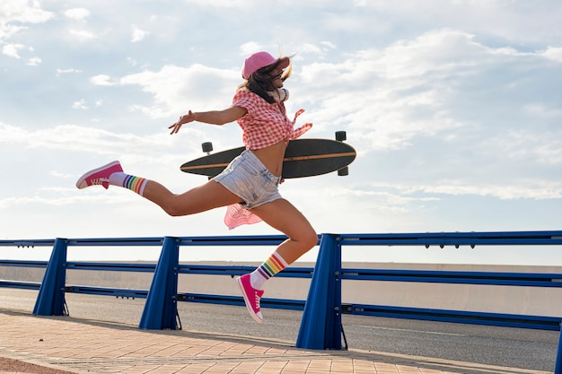 Beautiful girl with a cap and headphones with her skateboard in the street and movement in the air