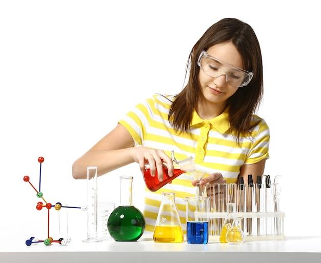 白で隔離される化学フラスコと試験管を持つ美しい少女
