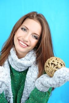 青い背景の上のクリスマスボールを持つ美しい少女