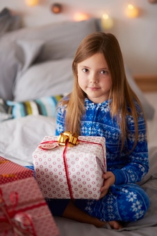 Beautiful girl with christmas present in the bed
