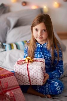 Красивая девушка с рождественским подарком в постели