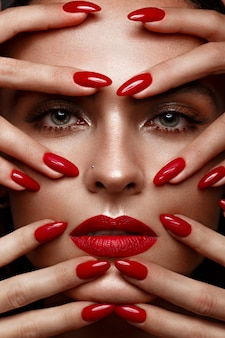 Beautiful girl with a classic makeup and red nails, manicure design, beauty face,