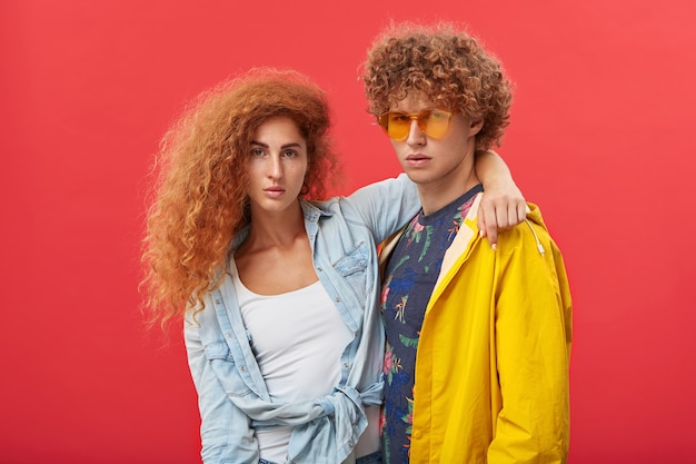 Beautiful girl with clean freckled skin and ginger voluminous hair embracing a red-haired man in eyewear