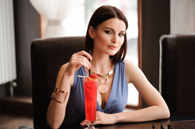 Beautiful girl with a cocktail at the cafe.