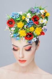 Красивая девушка с яркими цветами на голове и креативным макияжем, глядя вниз