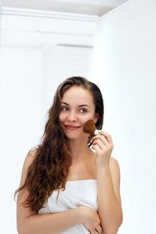 Красивая девушка с косметической пудрой для макияжа. составить. нанесение макияжа для идеальной кожи.