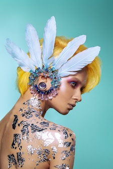 Красивая девушка с творческим макияжа и рисунком тела. окрашенные волосы, серьги и аксессуары для волос.