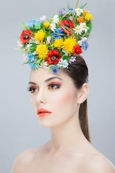 Красивая девушка с креативным макияжем и цветами на голове