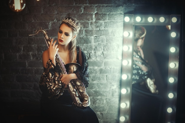 Beautiful girl with a crown on her head and a saxophone in the hands is posing with jazz music. international jazz festival