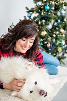 Beautiful girl with curls in a red-checked shirt laughs hugs a samoyed husky that licks on the cheek