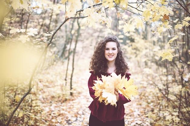 カエデの葉とスミリを保持している秋の公園の栗色のトップで巻き毛の黒い髪の美しい少女...