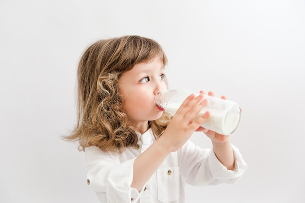 곱슬 머리와 파란 눈을 가진 아름 다운 소녀는 병에서 우유를 마신다.