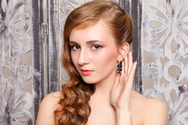 곱슬 머리와 붉은 입술을 가진 아름 다운 소녀입니다. 미용 및 에스테틱 케어. 갈색 머리를 위한 현대적인 스타일링. 귀걸이 장신구 및 액세서리
