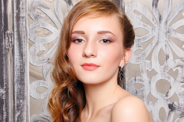 Красивая девушка с вьющимися волосами и красными губами. красота и эстетический уход. современная укладка для брюнетки. серьги, украшения и аксессуары